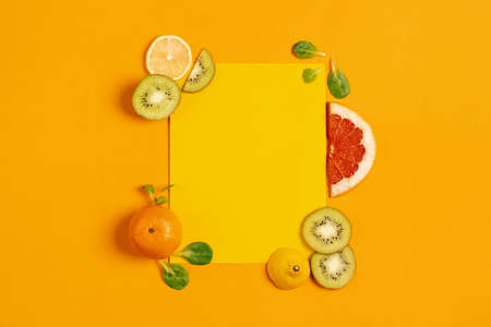 Composition of fruit, orange, lemon and kiwi on yellow background