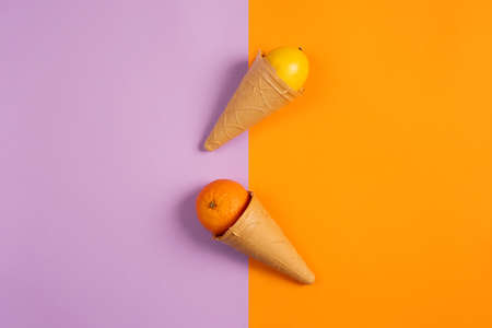 Ice cream with natural orange and lemon fruits. Concept of genuine and biologic fruit. Purple and yellow background