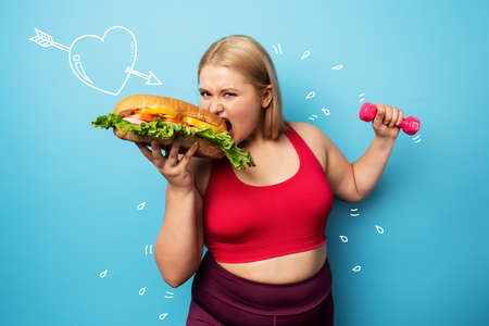 Fat girl does gym and want to eat a sandwich. Concept of indecision and doubt Archivio Fotografico
