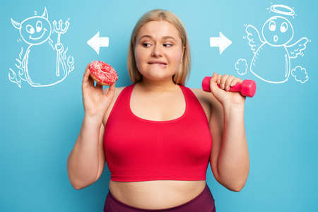 Fat girl thinks to eat donuts instead of does gym. Concept of indecision and doubt with angel and devil suggestion Banque d'images