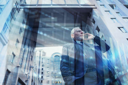 Senior businessman speaks on the mobile while walking in a modern city. Double exposure effect Stock Photo