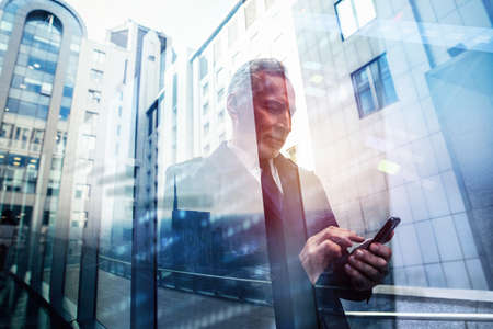 Busy senior business man uses mobile phone to communicate