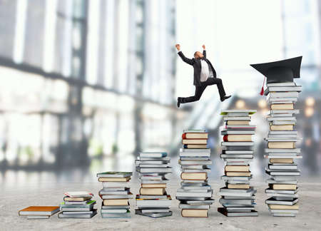 Business man reaches the graduation hat jumping on piles of books. Concept of success and determination on study