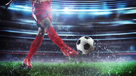 Soccer player kicks the ball vigorously at the stadium