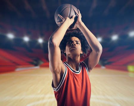 Young African American boy with basketball taking a free throw