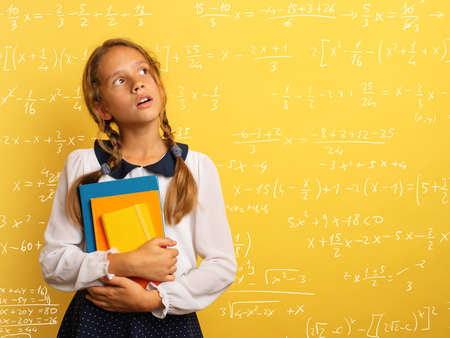 Young student is with shocked expression and think about complex exercises. Yellow background Stockfoto