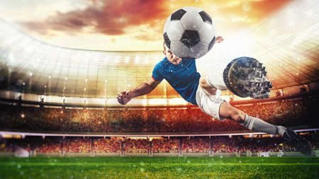 Soccer striker hits the ball with an acrobatic kick in the air at the stadium at sunset