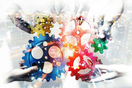 Business team connect pieces of gears. Teamwork, partnership and integration concept. double exposure with light effects Standard-Bild