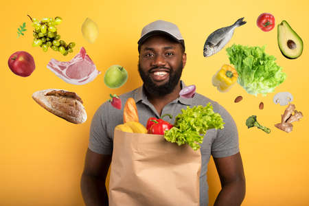 Deliveryman with happy expression ready to deliver bag with food. Yellow background. Standard-Bild