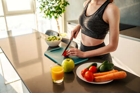 Athletic girl with gym clothes eats a salad in the kitchen Standard-Bild