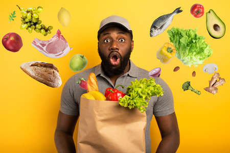 Deliveryman with wondered expression ready to deliver bag with food. Yellow background.