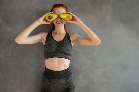 Athletic girl with gym clothes eats avocado at home. Standard-Bild