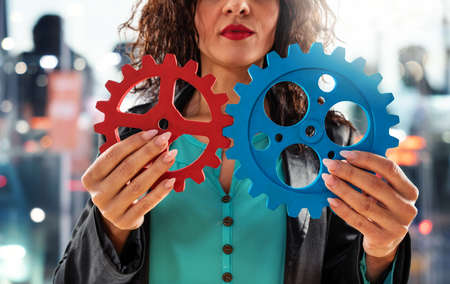 Businesswoman tries to work with gears. Concept of teamwork and partnership.