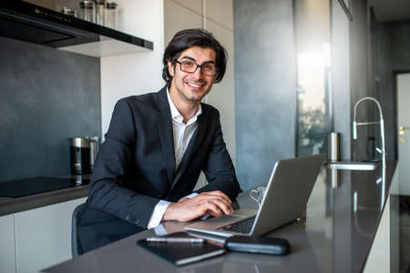Businessman works from remote at house with a laptop due to quarantine. Stock Photo