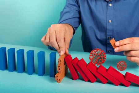 Concept of covid19 coronavirus pandemic with falling chain like a domino game. Contagion and infection progression stopped by a hand of a doctor. Cyan background Stock Photo