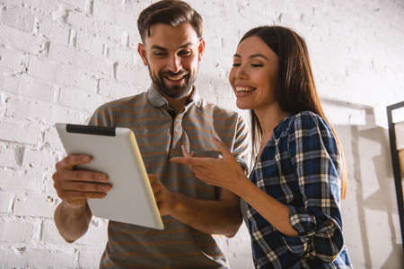 Two happy colleagues work with a tablet in office Stock Photo