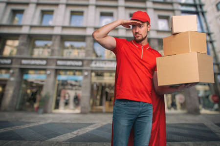 Red courier acts like a powerful superhero. Stock Photo