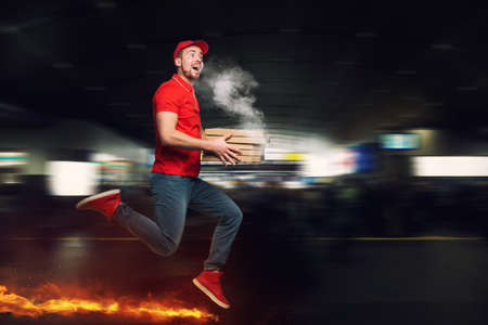 Messenger in red uniform runs on foot really fast to deliver quickly hot pizzas just baked