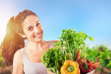 Girl with bag full of freshly bought vegetables with the vegetable garden on background
