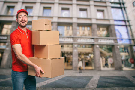 Red courier outside carries parcels for deliveries of shipments.