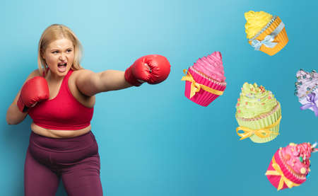 Fat girl in fitness suite does boxing and fight against cupcakes. Cyan background Stock Photo