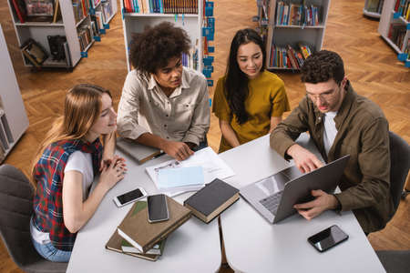 University students are studying in a library together. Concept of teamwork and preparation Stock Photo