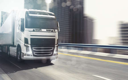 White truck moving fast on the highway with a modern city in the background