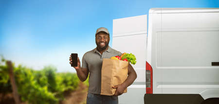 Delivery guy with a grocery bag full of food with the vegetable garden from which the products arrive Stock Photo
