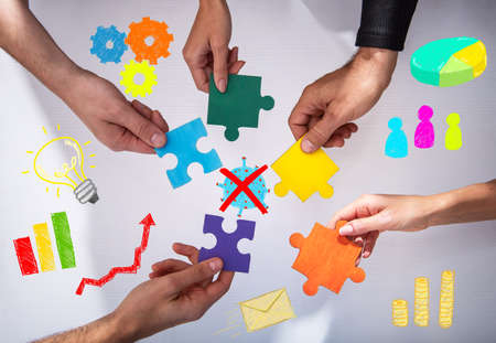 Businessmen working together to build a puzzle. Concept of teamwork, partnership, integration and startup. Stock Photo