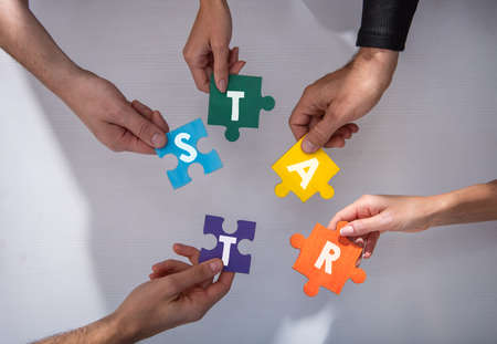 Businessmen working together to build a puzzle. Concept of teamwork, partnership, integration and startup. Standard-Bild