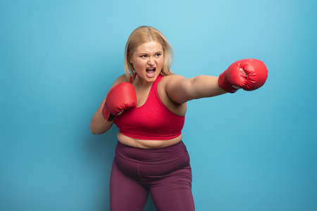 Fat girl in fitness suite does boxing. Cyan background