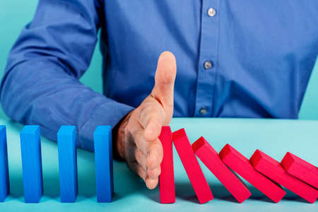 Businessman stops a chain fall like domino game toy. Concept of preventing crisis and failure in business