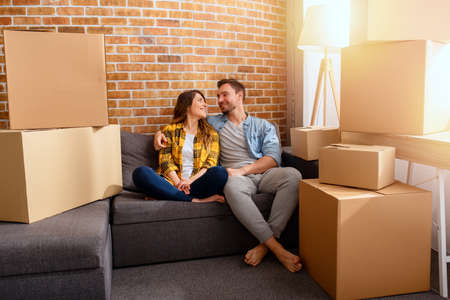 Happy couple have to move and arrange all the packages. Concept of success, change, positivity and future
