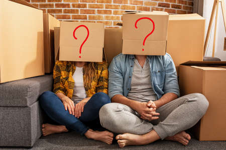 Confused couple of having to move and arrange all the packages to new home. Concept of success, confusion, change and future