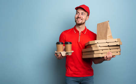 Courier is happy to deliver hot coffee and pizza. Cyan background Stock Photo