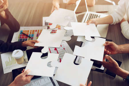 Businessmen working together to build a puzzle.