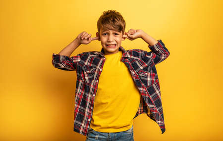Child covers his ears because he does not want to hear noise. Yellow background