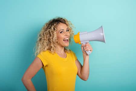 Woman speaks with loudspeaker. joyful expression. cyan background Foto de archivo