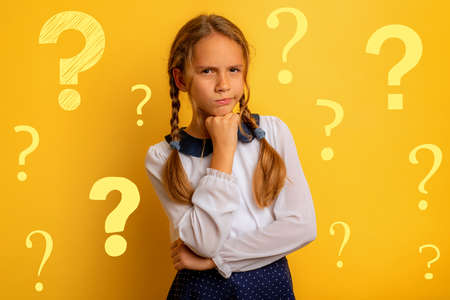 Young student has some doubt about something. yellow background