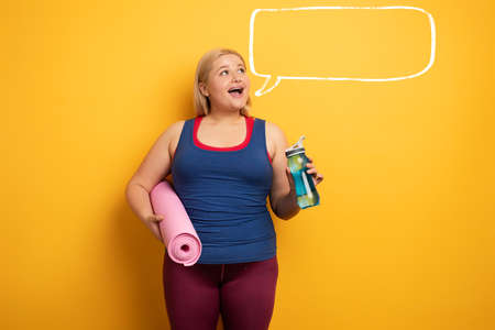 Fat girl does gym at home. satisfied expression. yellow background 免版税图像