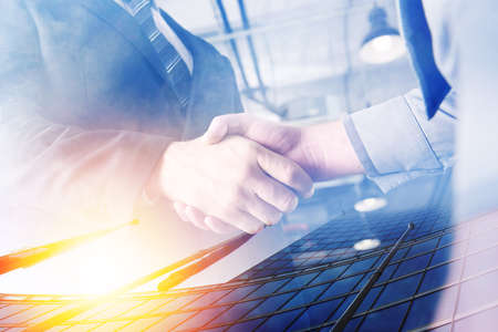 Two businessmen shake hands in agreement. Double exposure with light effect Фото со стока