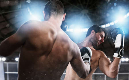 Boxer in a boxe competition beats his opponent. Stock Photo