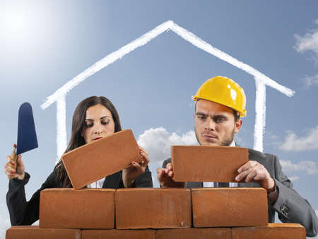 Couple works like masons to build a house to have a family 写真素材
