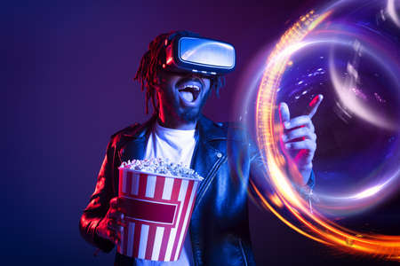 Man with VR glasses and popcorn watches a 3D film Stock Photo