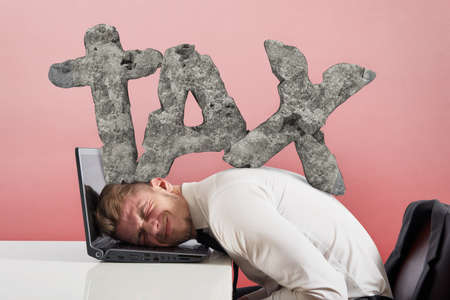 Businessman at work with his laptop is oppressed by the burden of taxes