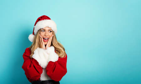 Woman with Santa Claus costume with surprised expression. cyan background