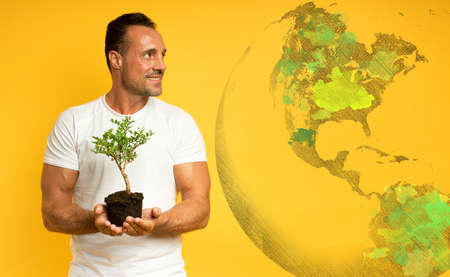 Happy man holds a small tree ready to be planted. concept of forestation, ecology and conservation