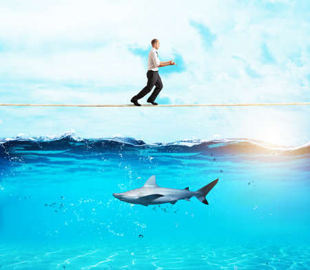 Worry man in balance walking on a rope over a shark