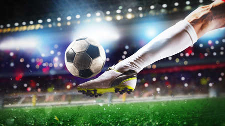Football scene at night match with close up of a soccer shoe hitting the ball with power Reklamní fotografie