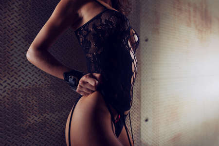 Sexy woman in lingerie and bdsm style with a grunge metal background